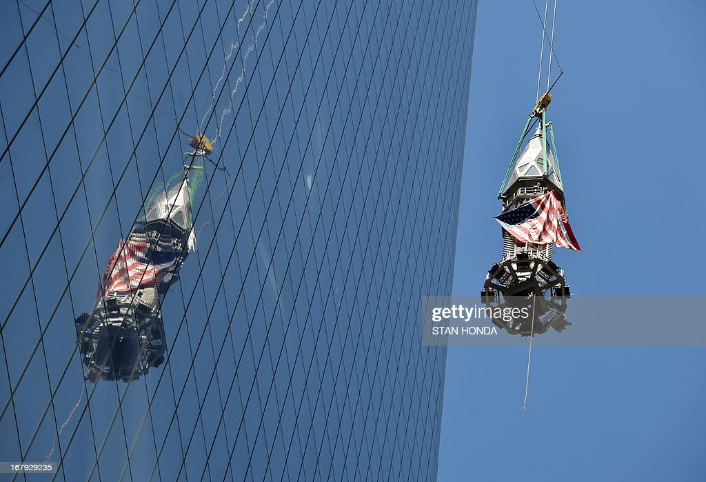 The final sections of the spire is raised to the top of One World Trade Center May 2, 2013 in New York to a temporary work platform atop the structure. Ironworkers will install the sections at a later date and when complete, One WTC will stand 1,776 feet (541 meters) high, making it the tallest building in the Western Hemisphere. AFP PHOTO/Stan HONDA