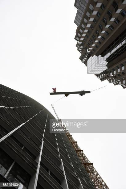 The final steel beam is hoisted up to the top of the building during a topping off ceremony for the Salesforce Tower in San Francisco California US...