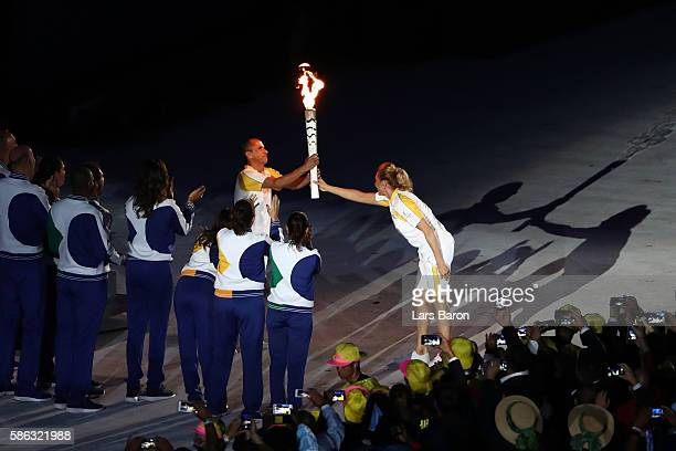The final torch bearer and former marathon runner Vanderlei Cordeiro de Lima is passed the Olympic torch by former during the Opening Ceremony of the...