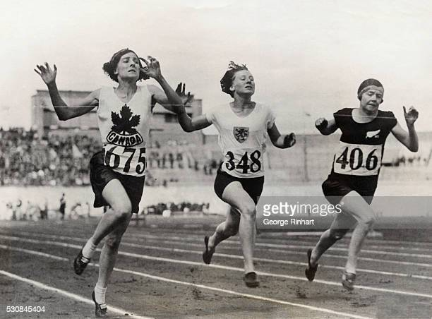 The finish of the eight heat of the 100meter dash for women won by Myrtle Cook of Canada second place taken by Miss Wilson of New Zealand and third...