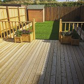 Brand new decking and artificial grass played in new build house's back garden. This image was taken on a mobile device