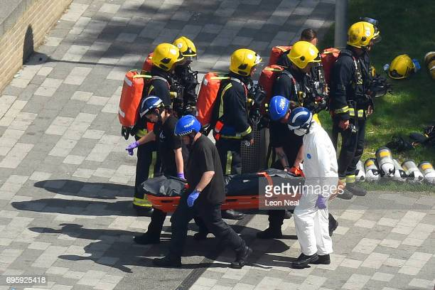 The fire crew stop as the Police forensics carry a body bag on a stretcher out of the 24 storey residential Grenfell Tower block in Latimer Road West...