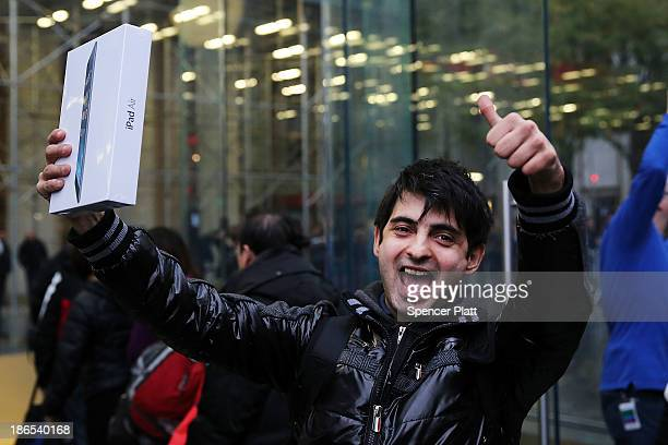 The first customer in line Rami Shamis holds up his new iPad Air at the Apple Store on November 1 2013 in New York City The new iPad which will also...