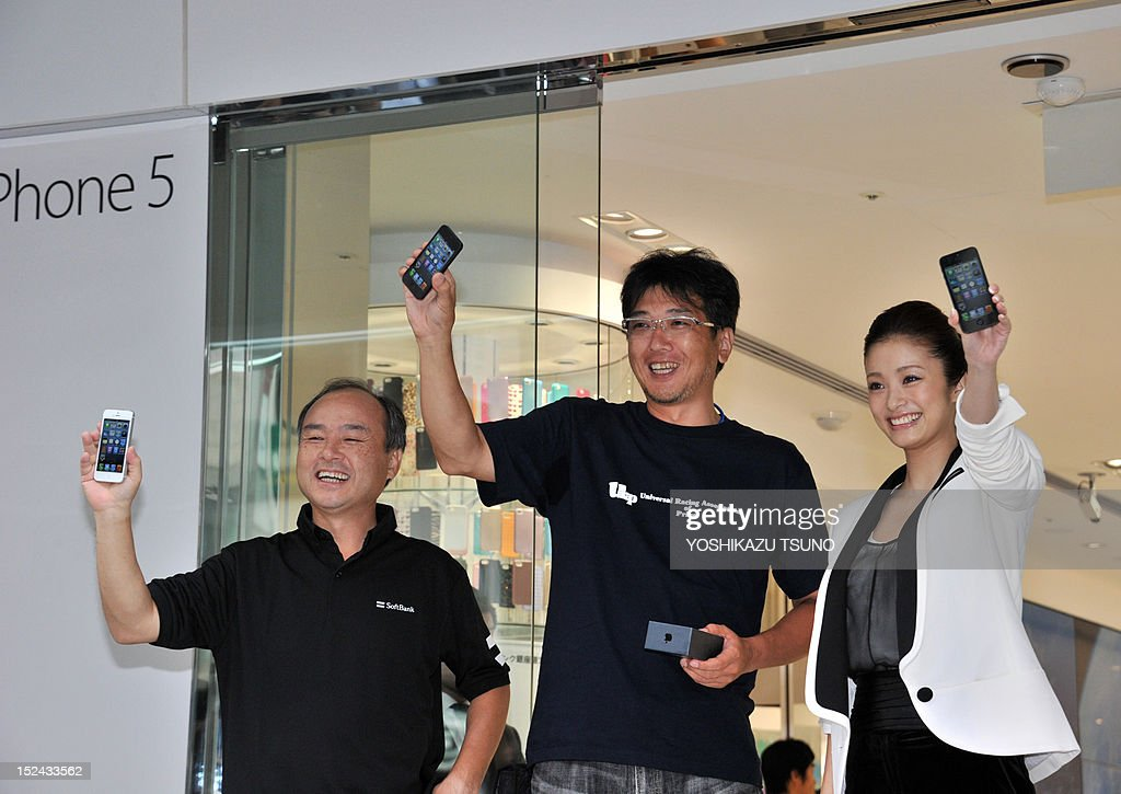 The first customer (C) receives Apple's new iPhone 5 smartphone from Softbank president Masayoshi Son (L) and actress Aya Ueto at a launching ceremony at the Softbank mobile phone shop in Tokyo on September 21, 2012. The iPhone 5 goes on sale on September 21 in Singapore, Sydney, US, Canada, France, Germany, Hong Kong, Japan and Britain. AFP PHOTO / Yoshikazu TSUNO