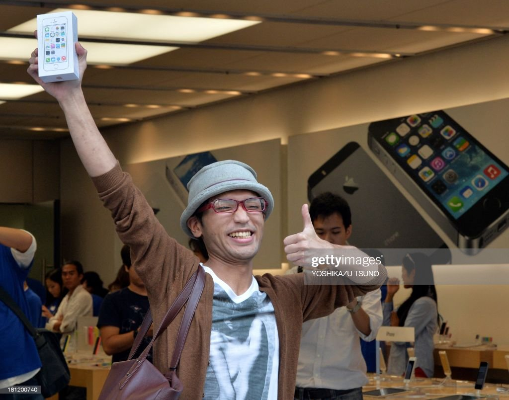 The first customer to buy Apple's new iPhone 5s smartphone gestures after his purchase at the Apple Store in Tokyo on September 20, 2013. Apple's new iPhone 5s and 'cheap' 5C models went on sale in Japan on September 20. AFP PHOTO / Yoshikazu TSUNO