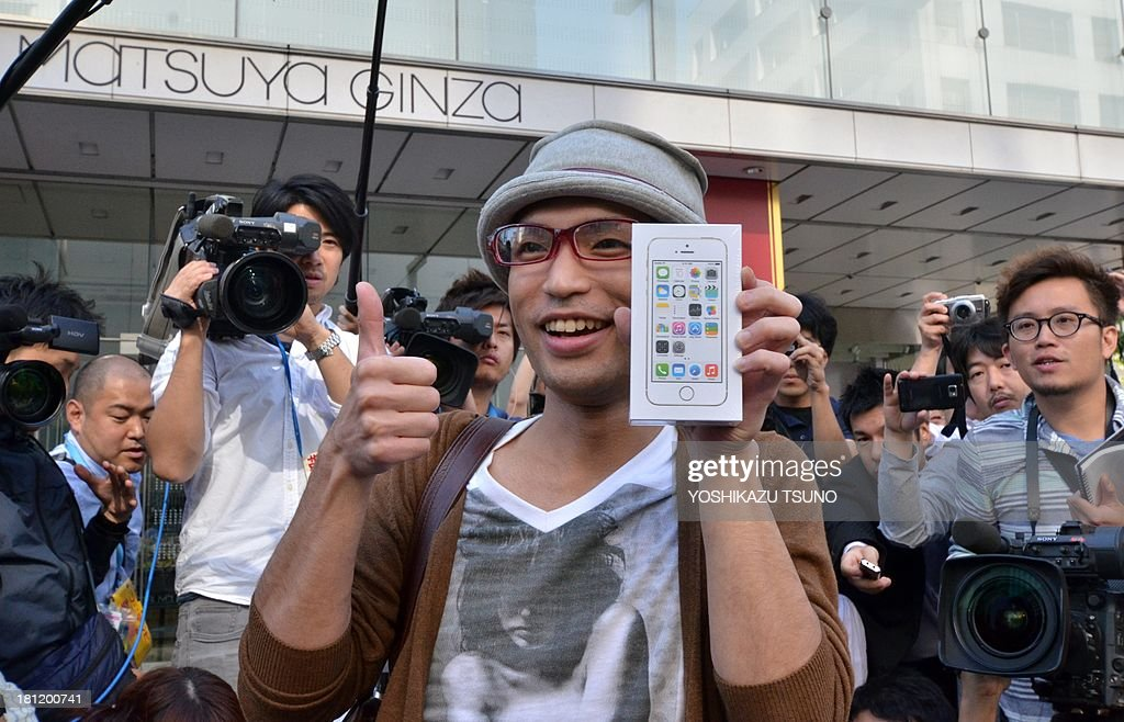 The first customer to buy Apple's new iPhone 5s smartphone poses with his phone after his purchase at the Apple Store in Tokyo on September 20, 2013. Apple's new iPhone 5s and 'cheap' 5C models went on sale in Japan on September 20. AFP PHOTO / Yoshikazu TSUNO