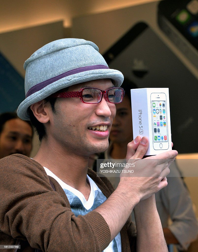 The first customer to buy Apple's new iPhone 5s smartphone poses with his purchase at the Apple Store in Tokyo on September 20, 2013. Apple's new iPhone 5s and 'cheap' 5C models went on sale in Japan on September 20. AFP PHOTO / Yoshikazu TSUNO