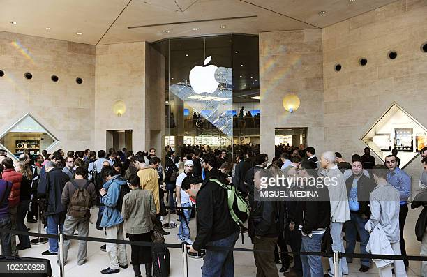 The first customers wait for the opening of the Apple store at the Carrousel du Louvre in Paris as the iPad goes on sale goes on sale on May 28 2010...