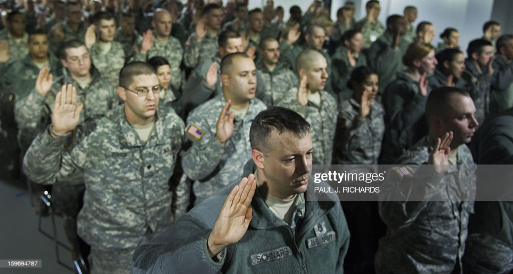 The first group of 6000, US National Guard Soldiers and Airmen from more than 25 US States, hold their right hands up as they take a legal oath to officially make them deputized 'special police officers' for the 57th Presidential Inauguration, during 'in-processing' at the DC National Guard Armory January 18, 2013, in Washington,DC. The National Guard will provide a myriad of support to civil authorities. Photo/Paul J. Richards