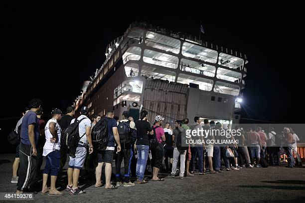 The first group of Syrian migrants wait to embark the Eleftherios Venizelos liner which will serve as registration and accommodation center at the...