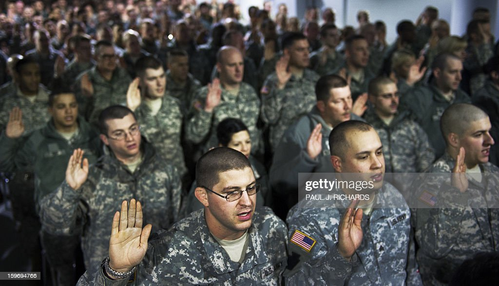The first group of US National Guard Soldiers and Airmen from more than 25 US States, hold their right hands up as they take a legal oath to officially make them deputized 'special police officers' for the 57th Presidential Inauguration, during 'in-processing' at the DC National Guard Armory January 18, 2013, in Washington,DC. The National Guard will provide a myriad of support to civil authorities. Photo/Paul J. Richards