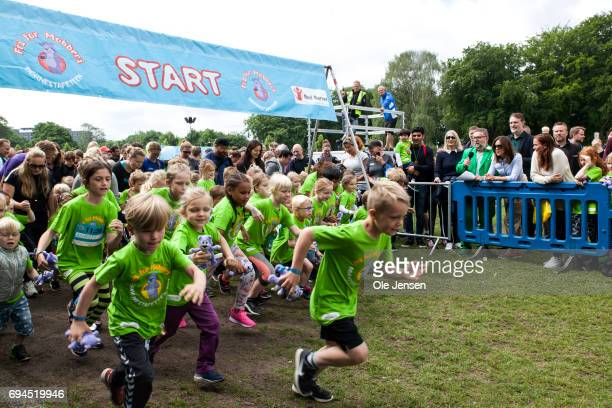 The first group of young runners starts out while Crown Princess Mary of Denmark is watching during the 'Children's Relay Run' in Faelledparken on...