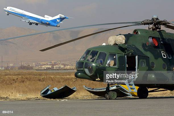 The first international Ariana Afghan Airlines flight in five years takes off from Kabul Airport over a military helicopter parked on the tarmac...