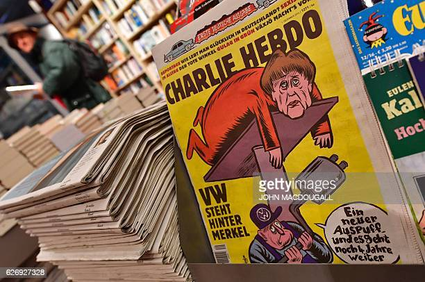 The first issues of the German version of French satirical weekly Charlie Hebdo are for sale at a newsstand in Berlin on December 1 2016 / AFP / John...