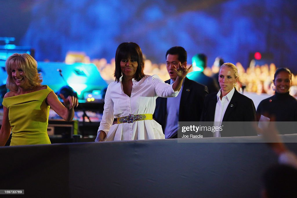The First Lady Michelle Obama and Jill Biden (in yellow) head to the stage during the children's concert at the Washington Convention Center to celebrate military families on January 19, 2013 in Washington, DC. The U.S. capital is preparing for the second inauguration of U.S. President Barack Obama, which will take place on January 21.