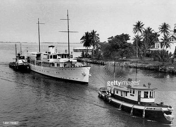 The first large yacht to go up the Miami River is towed by two tug boats