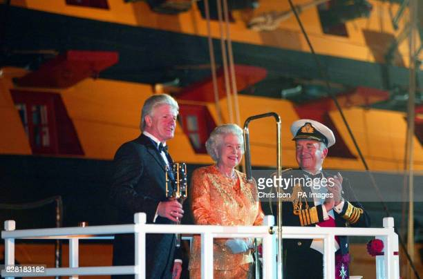 The first Sea Lord Admiral Sir Alan West applauds and Bruno Peek looks on as Britain's Queen Elizabeth II lights the Trafalgar Weekend Beacon during...