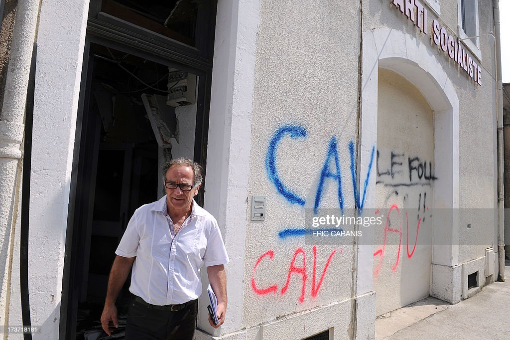 The first secretary of the Socialist Party's Aude Region Federation, Eric Andrieu, leaves the headquarters of his party destroyed after an overnight bomb explosion, on July 17, 2013 in Carcassonne.