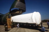 The first stage of a Titan IV launch vehicle is offloaded from a C5B Galaxy aircraft for an official acceptance and dedication ceremony The launch...