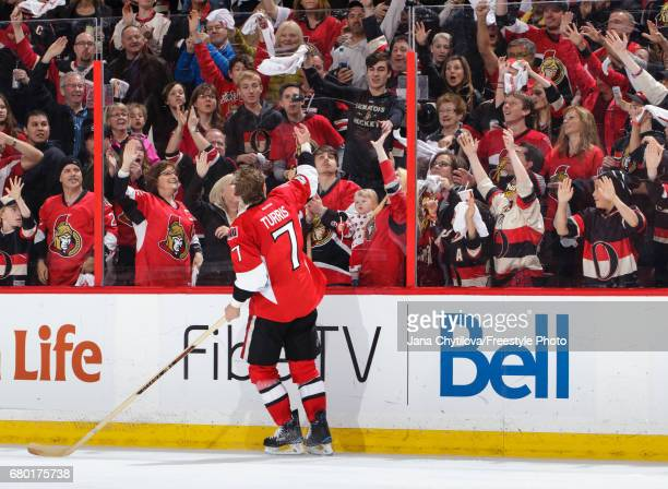 The first star of the game Kyle Turris of the Ottawa Senators tosses a puck over the glass for a fan following their overtime win against the New...