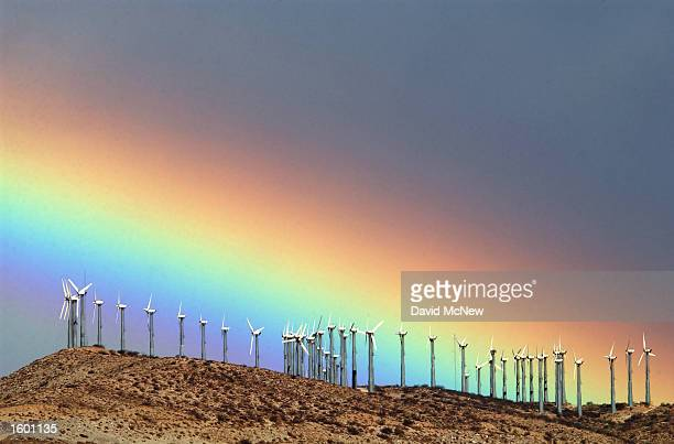 The first storm of the season produces a rainbow behind wind turbines in the San Gorgonio Pass November 9 2002 near Palm Springs California