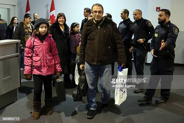 The first Syrian refugee family to disembark at Toronto Pearson International Airport makes their way into the Canada Border Services Agencys...