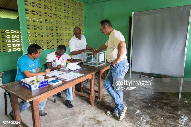 The first voter arrives to cast his ballot for the second round of the French presidential election at a polling station in Trou Poissons French...