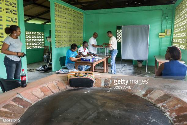 The first voter casts his ballot for the second round of the French presidential election at a polling station in Trou Poissons French Guiana on May...