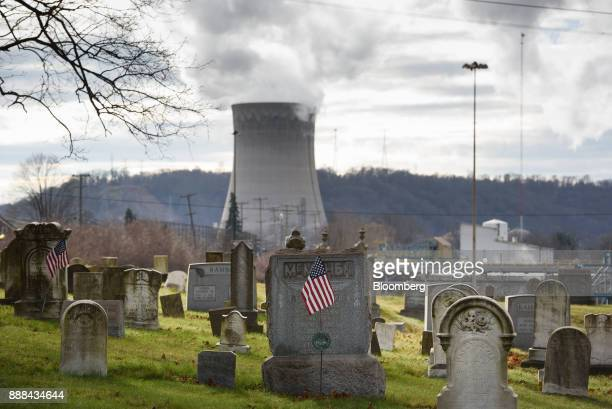 The FirstEnergy Corp Bruce Mansfield coalfired power plant stands past headstones at the Bethlehem Presbyterian Church cemetery in Shippingport...