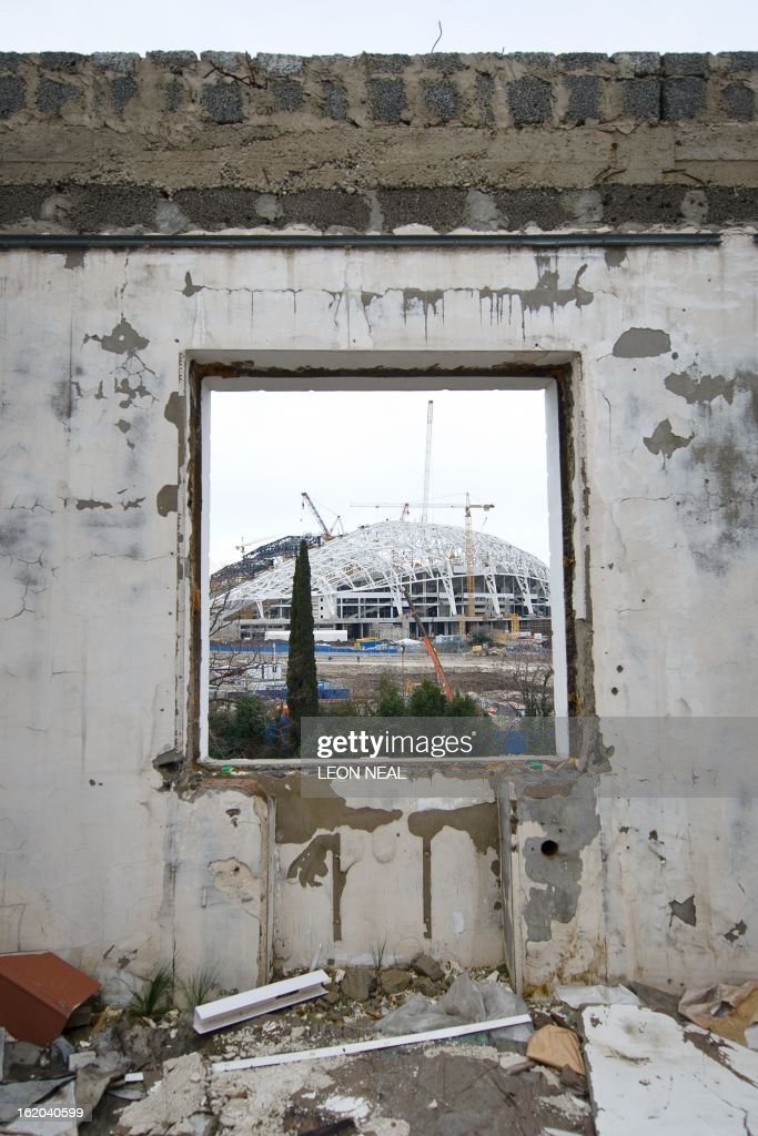The Fisht Olympic Stadium is seen through the window of a derelict house in the Adler district of Sochi, Russia, on February 18, 2013. With a year to go until the Sochi 2014 Winter Games, construction work and development continues as Olympic tests events and World Championship competitions are underway.