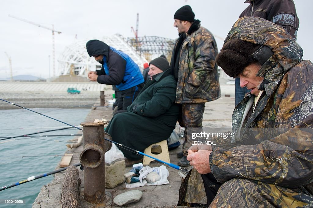 The Fishti Olympic Stadium is seen in the background as a group of men attempt to catch fish in Adler, a district of Sochi, Russia, on February 18, 2013. With a year to go until the Sochi 2014 Winter Games, construction work and development continues as Olympic tests events and World Championship competitions are underway. AFP PHOTO / LEON NEAL