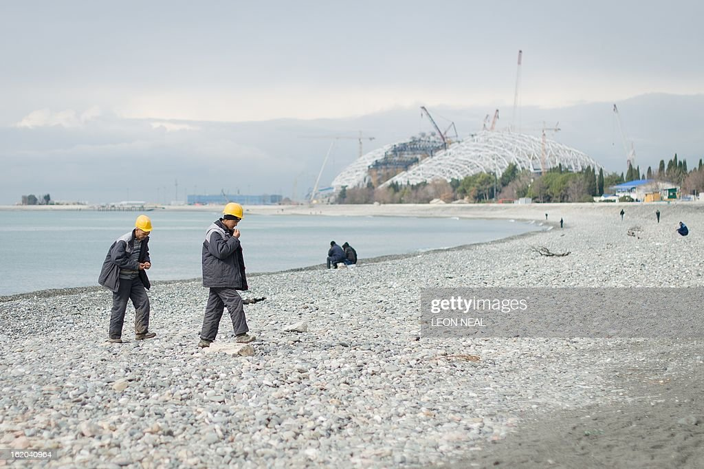 The Fishti Olympic Stadium is seen in the background as two workmen walk from the beach in Adler, a district of Sochi, Russia, on February 18, 2013. With a year to go until the Sochi 2014 Winter Games, construction work and development continues as Olympic tests events and World Championship competitions are underway.