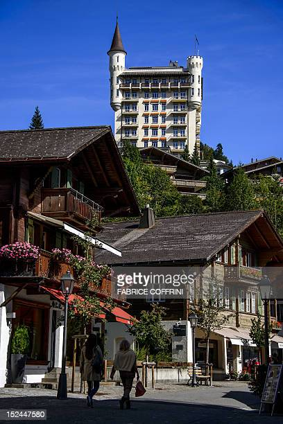 The fivestar hotel Gstaad Palace is pictured as people walk in a street of the Alpine resort of Gstaad in the canton of Bern on September 20 2012 The...