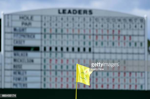 The flag blows in the breeze in front of a leaderboard on the 17th green during the first round of the 2017 Masters Tournament at Augusta National...