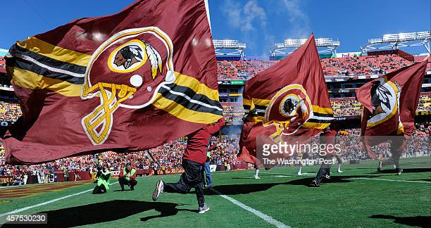 The flag crew runs onto the field before the game between the Washington Redskins and the Tennessee Titans at FedEx Field on Sunday October 19 2014