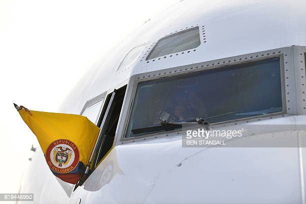 The flag of Colombia flies from the window of the President of Colmbia's Air Force plane as Colombian President Juan Manuel Santos and wife Maria...