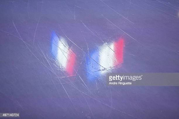 The flag of France is reflected in the ice during the playing of the French national anthem prior to an NHL game between of the Ottawa Senators and...