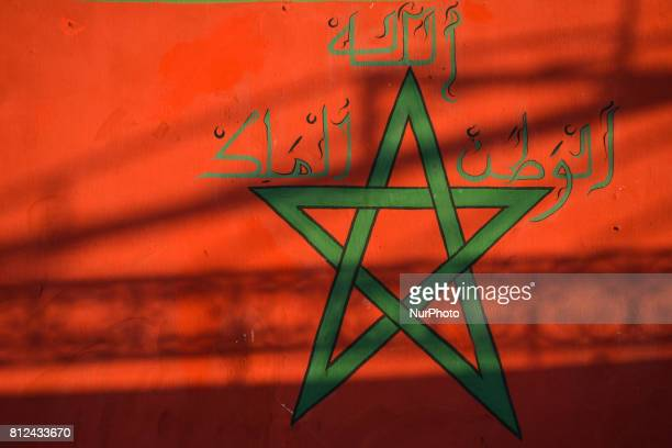 The flag of Morocco painted on a wall made of a red field with a blackbordered green pentagram representing the Seal of Solomon seen in Rabat's...