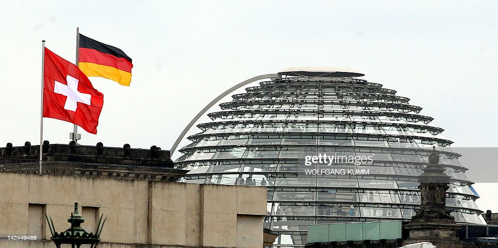 The flag of Switzerland flutters on the Swiss embassy in Berlin as in background can be seen the German flag and the cupola of the Reichstag housing the Bundestag (lower house of parliament) on April 5, 2012. Switzerland and Germany signed a revised tax accord toughening up penalties on tax cheats after several German states rejected the original deal. Under the accord, tax evaders will pay slightly more but their anonymity will be preserved, the German finance ministry said.