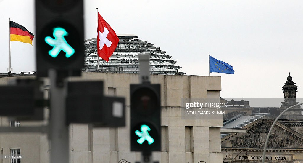 The flag of Switzerland flutters on the Swiss embassy in Berlin as in background can be seen the German flag and the cupola of the Reichstag housing the Bundestag (lower house of parliament) on April 5, 2012. Switzerland and Germany signed a revised tax accord toughening up penalties on tax cheats after several German states rejected the original deal. Under the accord, tax evaders will pay slightly more but their anonymity will be preserved, the German finance ministry said. AFP PHOTO / WOLFGANG KUMM GERMANY OUT
