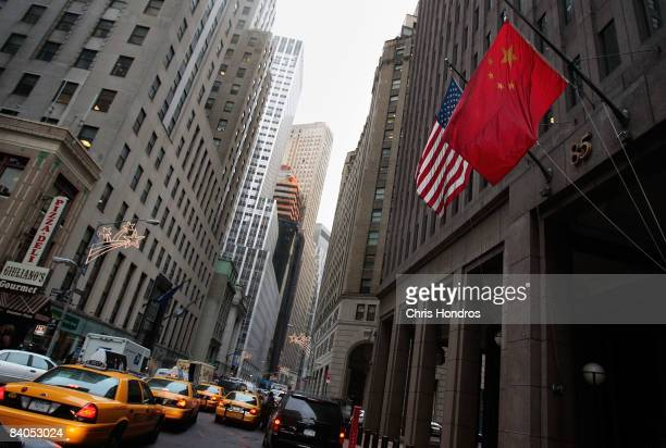 The flag of the People's Republic of China hangs next to an American flag outside the Goldman Sachs headquarters building December 16 2008 in New...