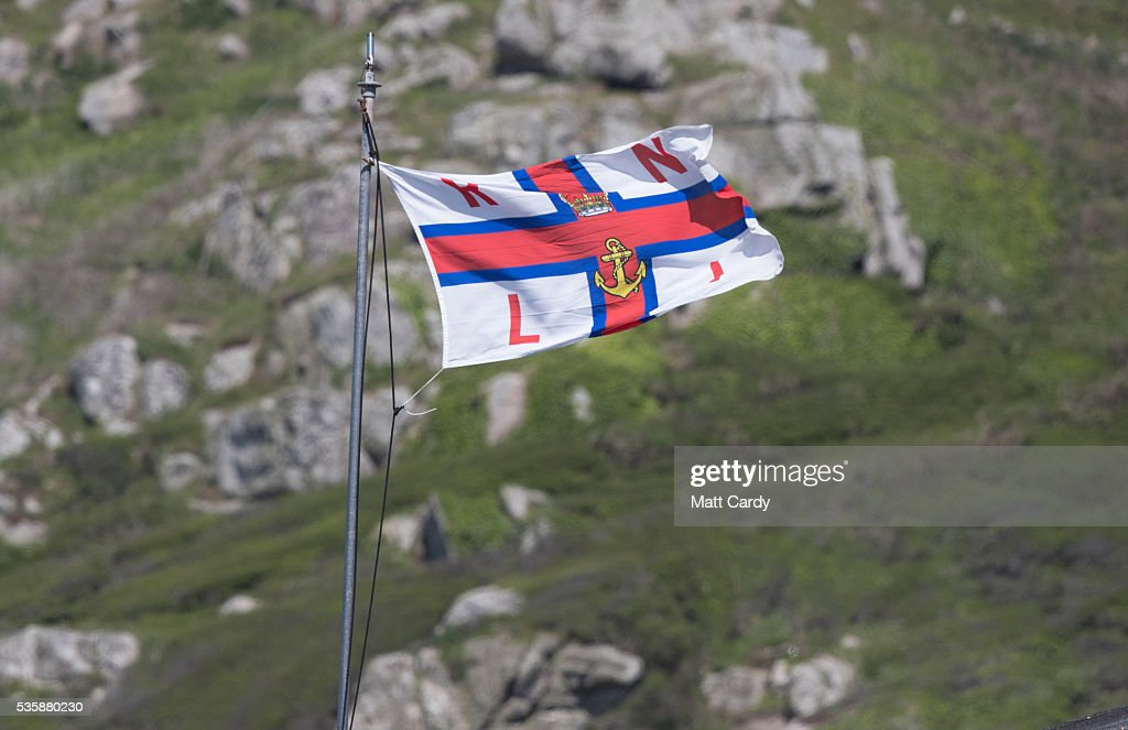 The flag of the RNLI flies as people swim and surf in the sea as they enjoy the fine weather at Sennen Cove on May 30, 2016 in Cornwall, England. As some parts of the UK were bathed in sunshine for the bank holiday weather forecasters have warned that gale-force winds and thunderstorms will sweep in from the east overnight.