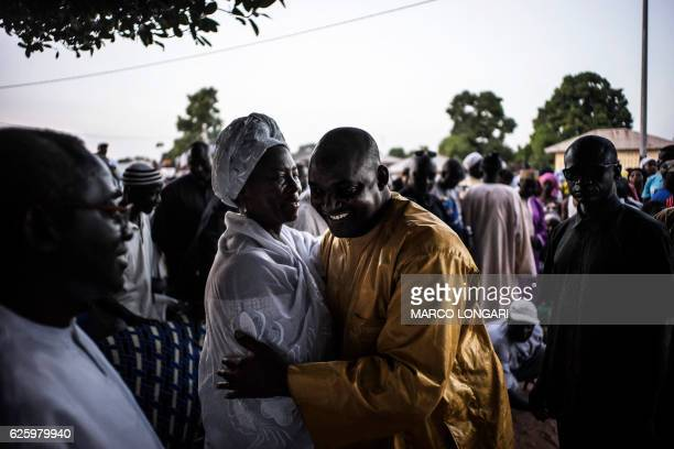 The flagbearer of the coalition of the seven opposition political parties in Gambia Adama Barrow is greeted by Gambian opposition figure Isatou...