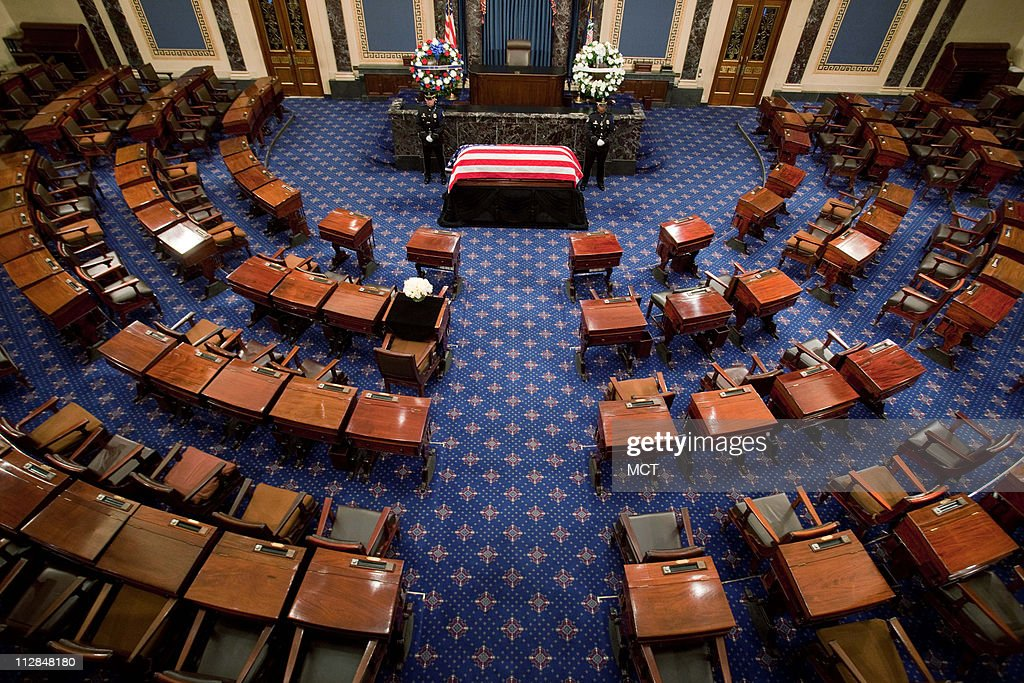 The flagdraped coffin of Sen Robert Byrd lies in repose as his desk is draped in black in the Senate Chamber of the US Capitol in Washington DC on...