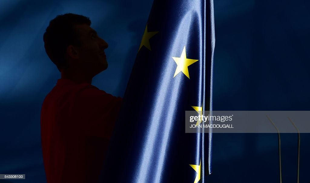 The flags, including the EU flag, are taken down after a press conference at the chancellery in Berlin, on June 27, 2016. Britain's shock decision to leave the EU forces German Chancellor Angela Merkel into the spotlight to save the bloc, but true to her reputation for prudence, she said she would act neither hastily nor nastily. / AFP / John MACDOUGALL