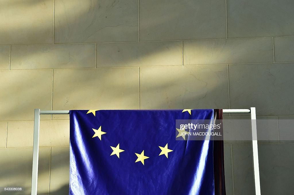 The flags, including the EU flag, are taken down and folded after a press conference at the chancellery in Berlin, on June 27, 2016. Britain's shock decision to leave the EU forces German Chancellor Angela Merkel into the spotlight to save the bloc, but true to her reputation for prudence, she said she would act neither hastily nor nastily. / AFP / John MACDOUGALL