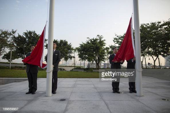 The flags of China left and Hong Kong are prepared for raising during a daily ceremony at Golden Bauhinia Square in Hong Kong China on Wednesday Jan...