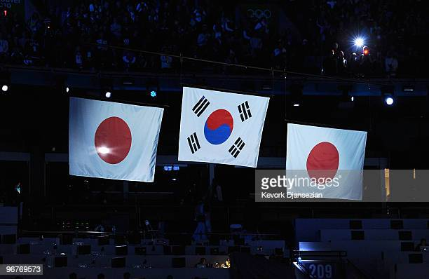 The flags of Japan and South Korea are raised during the playing of the National Anthem of South Korea at the medal ceremony for the Men's 500m Speed...