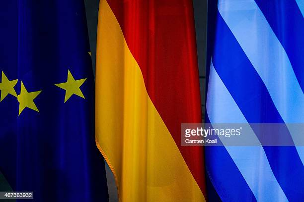 The flags of the European Union Greece and Germany stays beside as German Chancellor Angela Merkel and Greek Prime Minister Alexis Tsipras speak to...