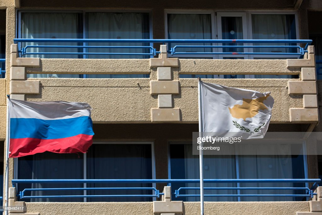 The flags of the Russian Federation, left, and Cyprus fly from flagpoles outside residential apartments in Limassol, Cyprus, on Tuesday, April 8, 2014. Cyprus wants to shield financial flows with Russia, where it's the biggest foreign investor, as the U.S. and the European Union ratchet up sanctions in response to President Vladimir Putin's annexing Crimea from Ukraine. Photographer: Andrew Caballero-Reynolds/Bloomberg via Getty Images